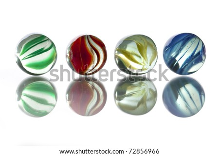 five glass marbles: green, red, yellow, blue on white background - stock photo
