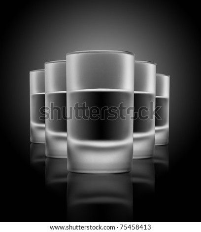 Five glasses of beverage on a glass table - stock photo
