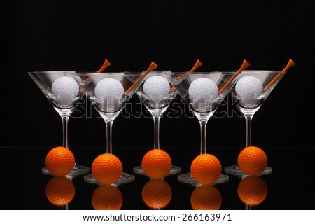 Five glasses of champagne with golf balls - stock photo