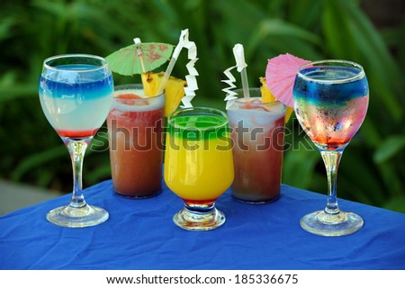 Five glasses of cocktail on a blue covered table and green background - stock photo