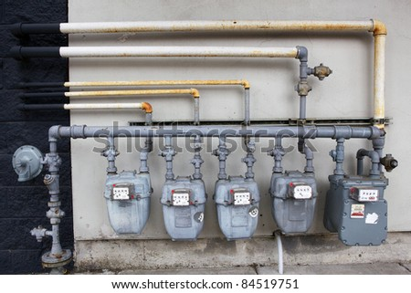 Five gray gas meters against a black and white wall - stock photo