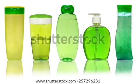 Five Green Plastic Bottles With Shampoo, Liquid Soap, Shower Gel. Isolated on white background with reflection. - stock photo