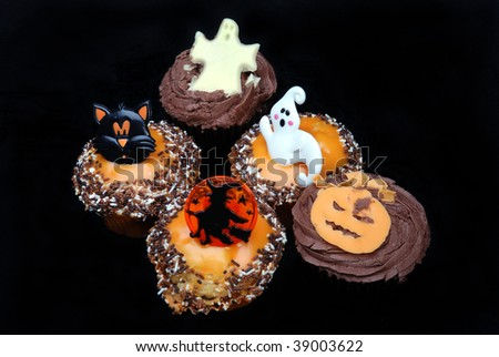 five halloween cakes on a black background.