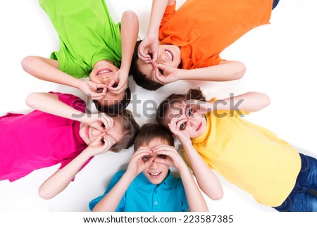 Five happy children lying on the floor in a circle with hands near eyes in bright t-shirts. Top view. Isolated on white. - stock photo