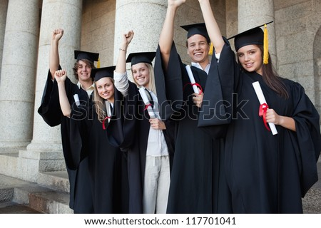 Five happy graduates posing the arm raised in front of the university - stock photo