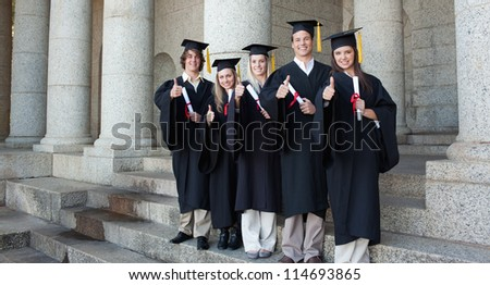 Five happy graduates posing the thumb-up in front of the university - stock photo