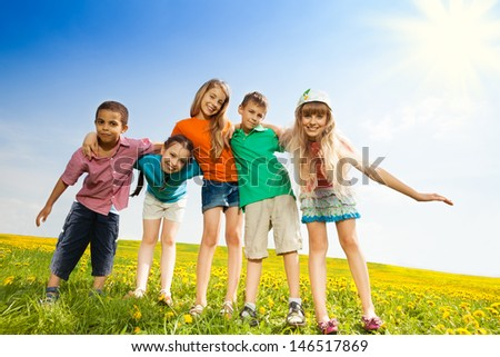 Five happy kids, boys and girls hugging together standing in the yellow flower field - stock photo