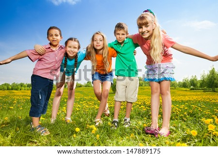 Five happy kids hugging together standing in the dandelion field - stock photo