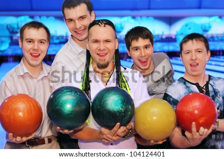 Five happy men hold balls in bowling club; friends relax together - stock photo