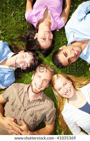 Five happy students lying on green grass