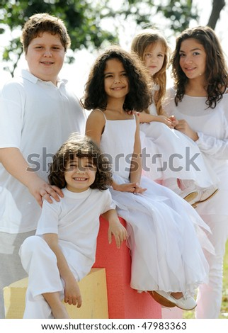 Five happy young children with white clothes sitting on colorful cubes, sun reflection in hair, back-light, shallow depth of field