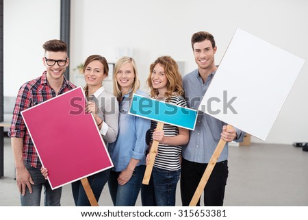 Five Happy Young Employees Holding Three Placards with Copy Space for Texts and Looking at the Camera. - stock photo