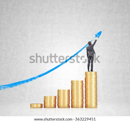 Five heaps of golden coins arranged as a bar chart, a businesswoman standing on the highest and painting a blue graph at the concrete background. Concept of career growth. - stock photo