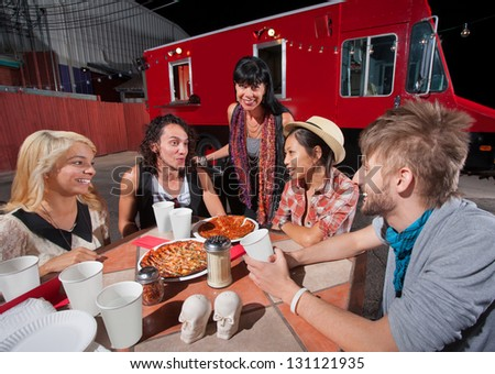 Five hipsters at mobile pizza restaurant with plates of food - stock photo