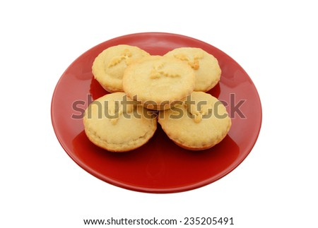 Five homemade mince pies on a festive red plate, isolated on a white background - stock photo