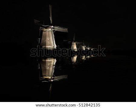 Five illuminated windmills, lighted by floodlights, with reflection in the water of the canal in the dark black night creating an almost surreal landscape in Kinderdijk, the Netherlands.