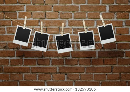 Five instant blank photographs hanging on a clothesline over brick wall with clipping path for the inside of the frames - stock photo