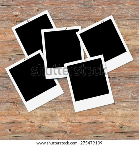 Five instant photo frames on brown wooden wall, free space for pictures