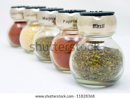Five jars with different spices lined-up diagonal - stock photo