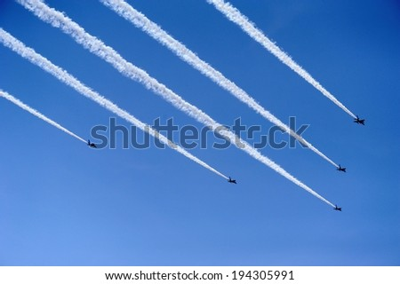 Five jets flying with smoky streams trailing behind. - stock photo