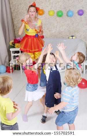 Five kids catch soap bubbles, which lets entertainer at children party. - stock photo