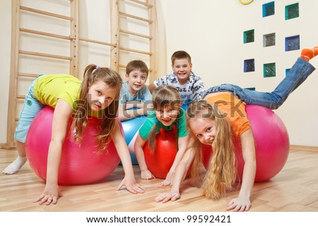 Five kids playing with gymnastic balls - stock photo