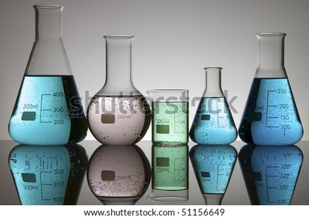 five laboratory flasks with liquid and a white background