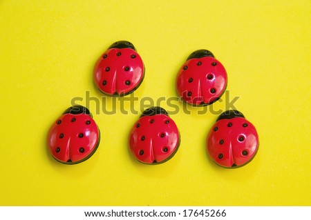 five ladybag buttons on yellow background - stock photo