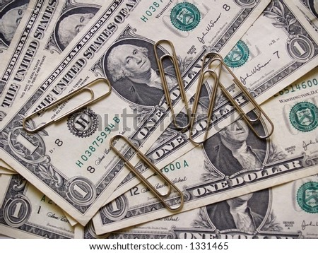 Five large steel paperclips against a background of US currency or money in the form of dollar bills.