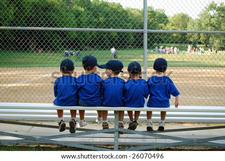 five little boys sit on a bench and wait for their baseball / t-ball game to begin - stock photo