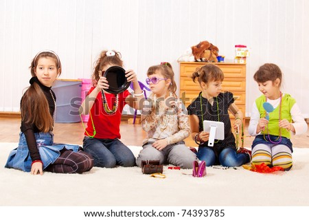 Five little girls trying on jewelry - stock photo