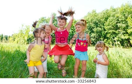 Five little preschool friends jumping in the grass - stock photo