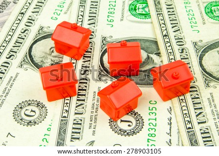 Five little red houses made of plastic are laying on one dollar banknote - stock photo