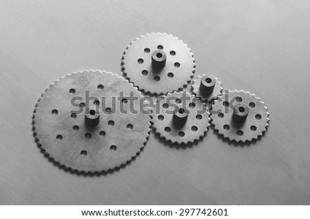 Five metallic gears on black and white - stock photo