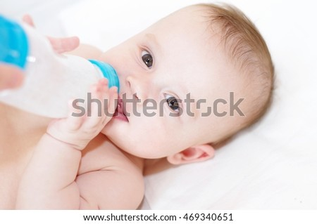 five-months baby eats from a small bottle himself