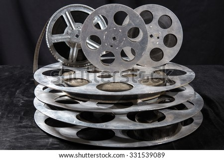 five Movie reel on a black background - stock photo