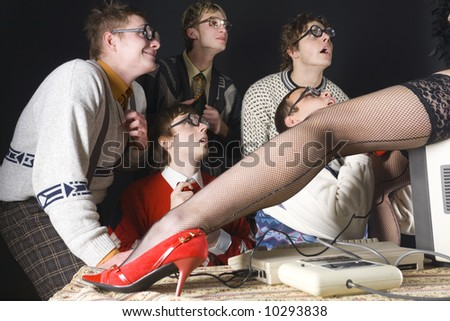 Five nerdy guys looking at stripteaser who is sitting on monitor. They are smiling and looking fascinated. Side view - stock photo