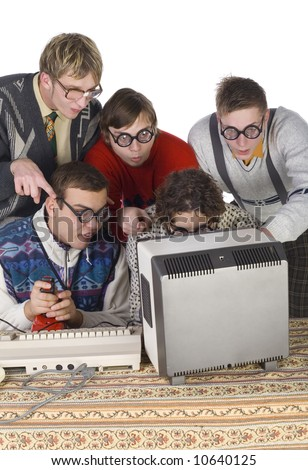 Five nerdy guys sitting and standing in front of old-fashioned computer. They are looking surprised to mointor. One of them is holding joystick. Front view, white background - stock photo