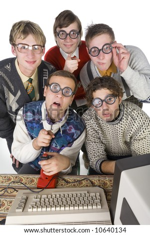 Five nerdy guys sitting in front of old-fashioned computer. They are looking at camera. One of them is pointing at camera. Front view, white background - stock photo