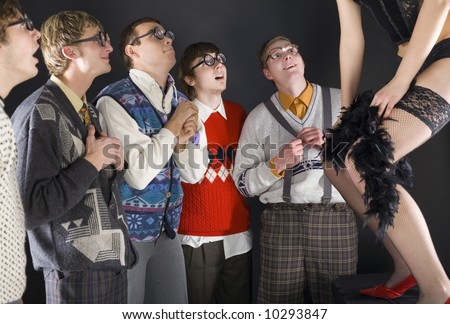 Five nerdy guys standing in front of dancing stripteaser. They are smiling and looking fascinated. Side view - stock photo