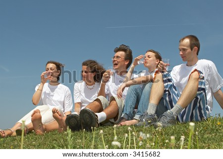 Five nice young people in white vests sit on a grass and drink water from plastic glasses