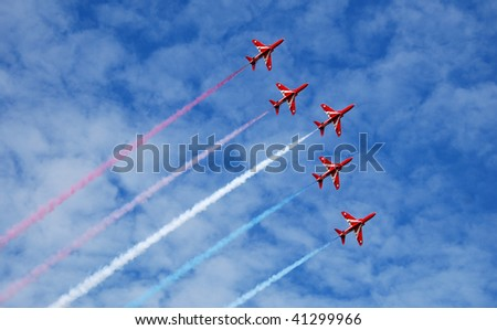 Five of the RAF display team The Red Arrows fly in formation across a summer sky. - stock photo