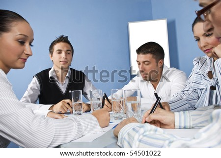 Five office workers  working hard  at business meeting,they talk,write ,look or read their paperwork - stock photo