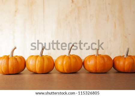 Five orange pumpkins sit in a row in front of a distressed, wooden background. - stock photo