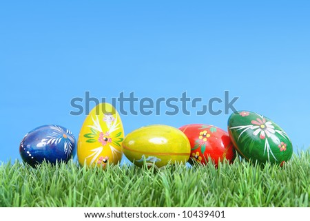Five painted easter eggs in grass over blue sky