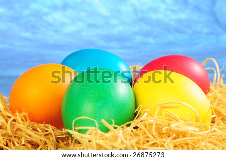 five painted eggs on a straw on a blue background
