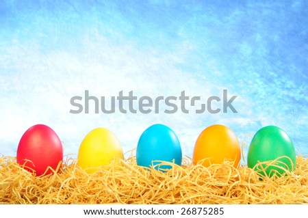 five painted eggs on a straw on a clear sky background