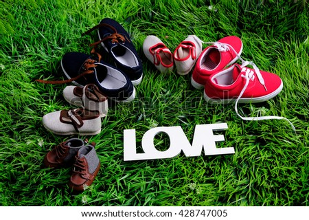 five pair of shoes in father big, mother medium and son or daughter small kid size on green grass, representing family, growth, education and togetherness concept