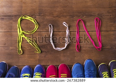Five pairs of running shoes and shoelaces run sign on a wooden floor background - stock photo