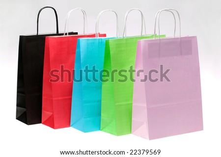 Five paper shopping bags with brights colours in a row at an angle. - stock photo